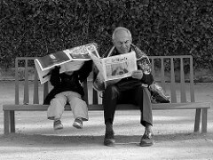 boy and grandfather reading on bench