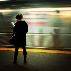 Woman Reading on Subway Platform